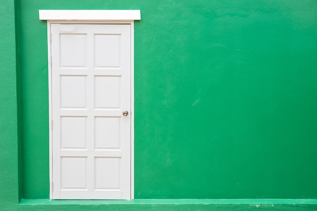 White door classic vintage on the color green wall background