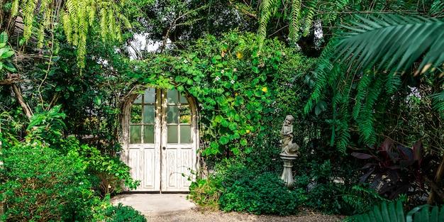녹색 나무와 정원에서 화창한 날에 식물 화이트 도어. 자연과 판타지 배경.