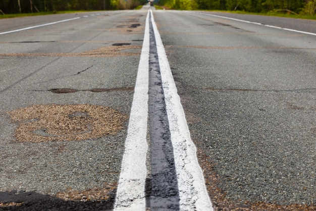 White double continuous strip on the asphalt