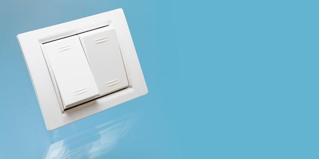Белый двойной электрический выключатель с отражением на синем фоне. крупный план. электротехника и промышленность. скопируйте пространство.