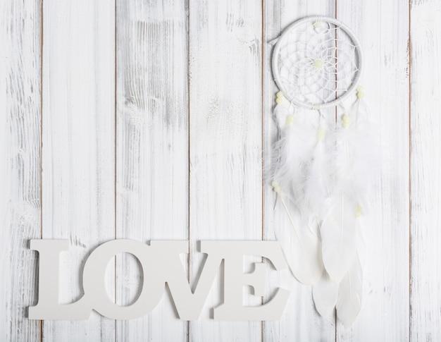 白いドリームキャッチャーと木製のテーブル、愛のテキストが横たわっていた