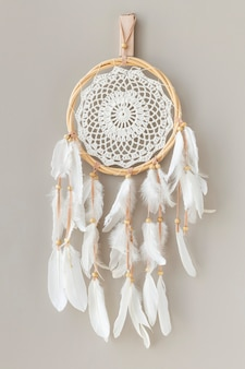 White dream catcher hanging on a off white wall