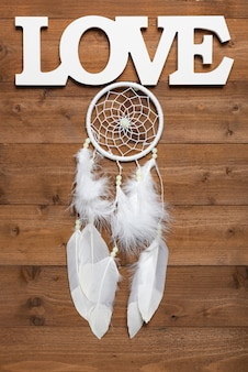 White dream catcher and love text on wooden table, flat lay