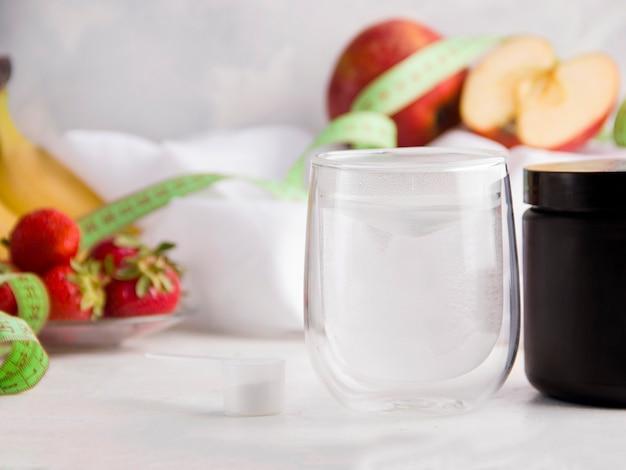 Белый напиток для людей, занимающихся спортом на белом фоне рядом с разными фруктами