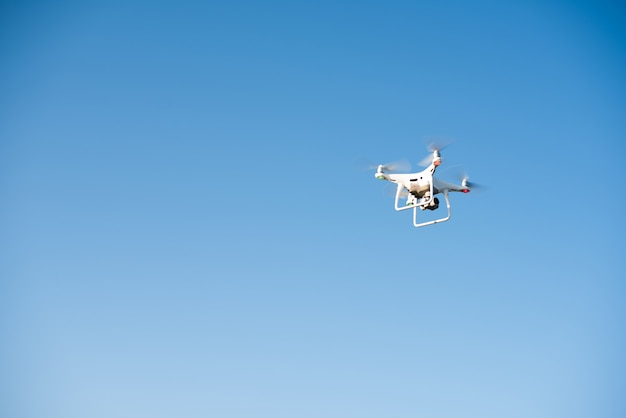 White drone fly in the sky recording a video