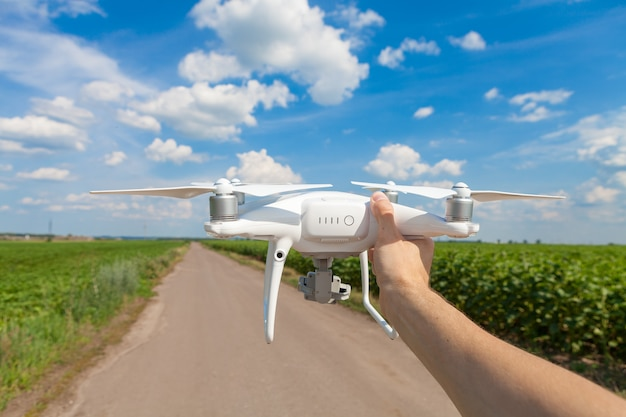 The white drone in hands at the man isolated against the background of the green field