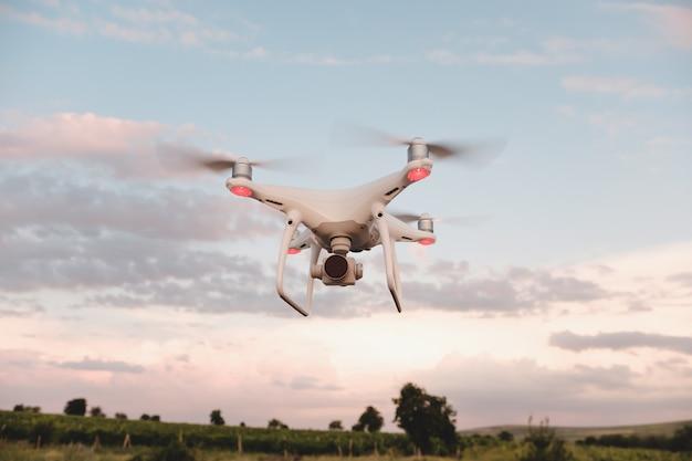Drone bianco in bilico in un cielo blu brillante