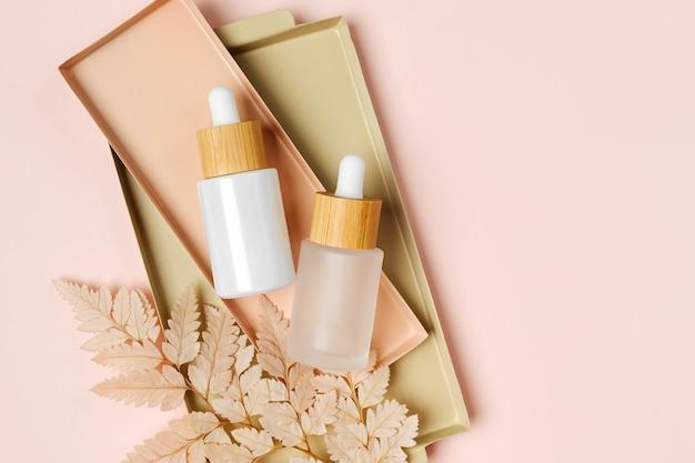 Белый макет бутылочек-капельниц с бежевым листом на пастельном фоне