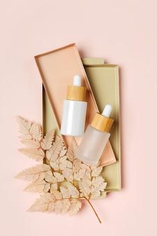 White dropper bottles mockup with beige leaf on pastel background