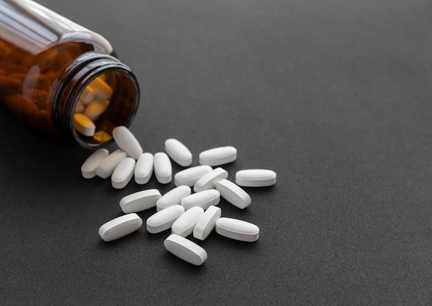 갈색 병에서 흘리 고 흰 약 알 약. 글로벌 건강 관리 개념