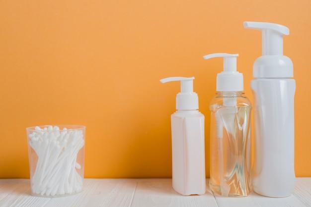 White ear buds with soap dispenser bottles on white table