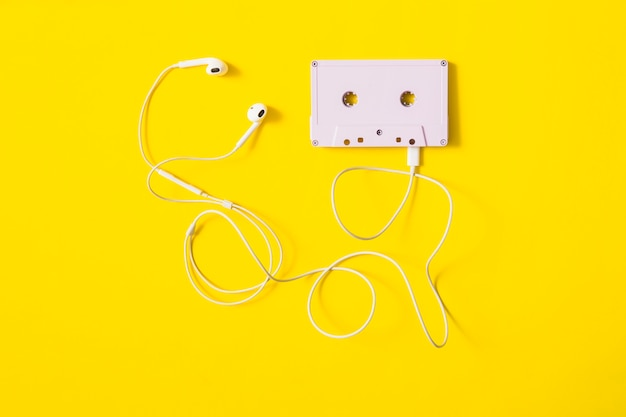 White ear phone connected to cassette tape on yellow background