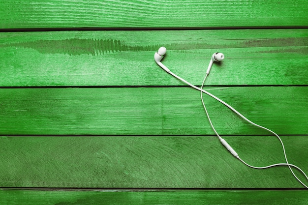 White earphones on green wooden table background