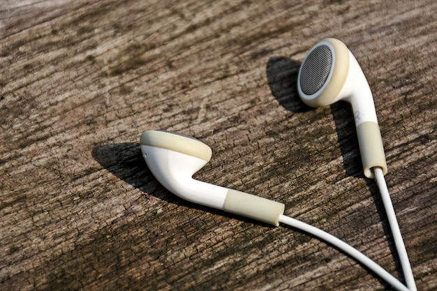 White earphones on old wood background