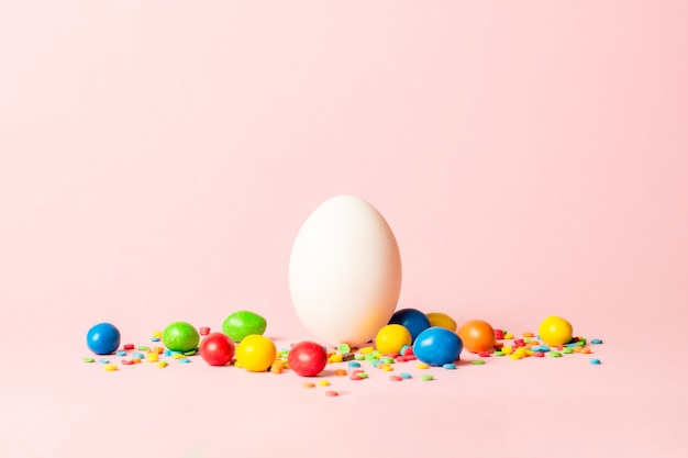 White easter egg and multi colored sweets on a pink surface. easter celebration concept.
