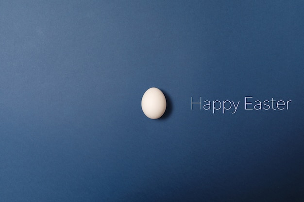 White easter egg with happy easter word, holiday concept. blue background.