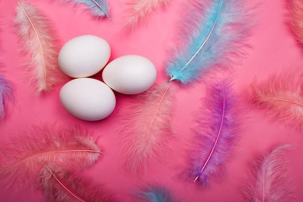 ピンクの表面に白いイースターエッグと鳥の色とりどりの繊細な羽
