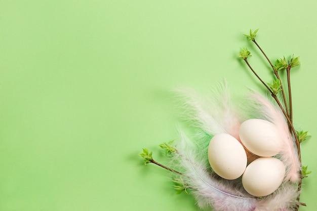 広げられた葉のつぼみを持つ色の羽の繊細な巣の白いイースターエッグ