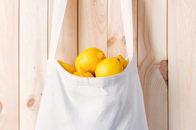 レモンでいっぱいの白いエコバッグは、木製の壁のクローズアップに掛かっています