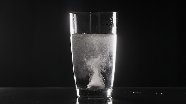 テーブルの上に水とガラスの白い発泡錠
