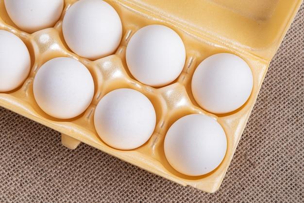 Scatola di uova bianche sulla superficie marrone