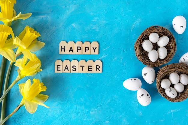 Пасха белое яйцо и желтые цветы на синем фоне с текстом.