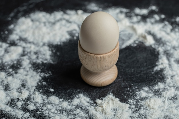 White egg in egg cup on floury background.