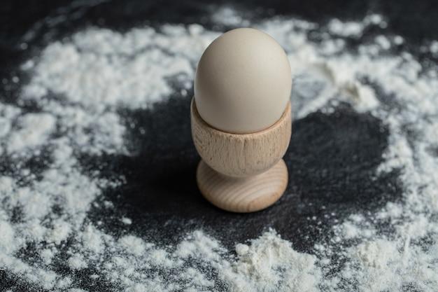 小麦粉の背景にエッグカップの白い卵。