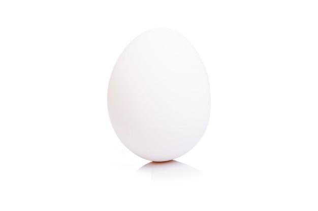 孤立した白い壁に白い卵。閉じる。テキストのためのスペース。