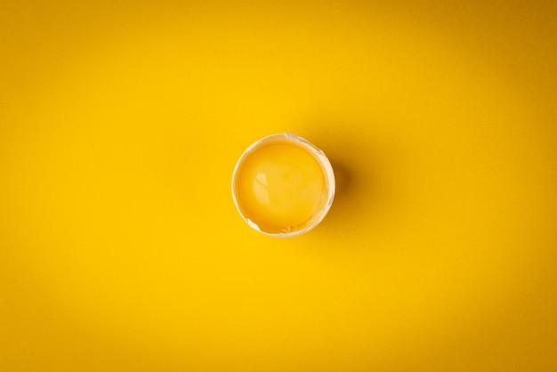 Белое яйцо на желтом фоне.