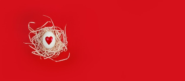 White egg with heart shape in decorative nest on a red background with copy space.