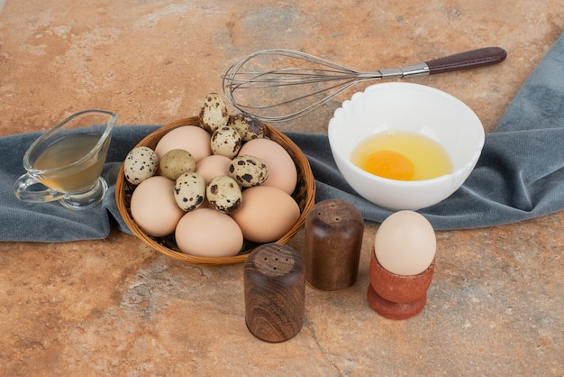 흰 접시에 노른자와 바구니에 흰 계란과 메추라기 달걀