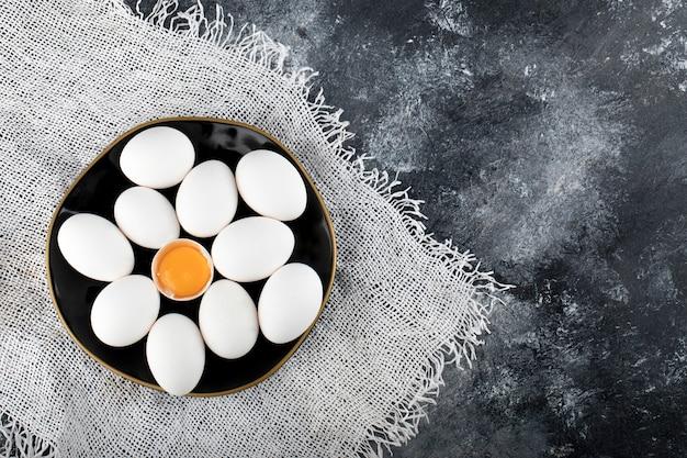 Белые яйца и желток на черной тарелке.