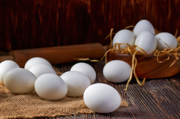 White eggs on burlap and wooden table. in the background are eggs in a wooden bowl and a rolling pin. low key.