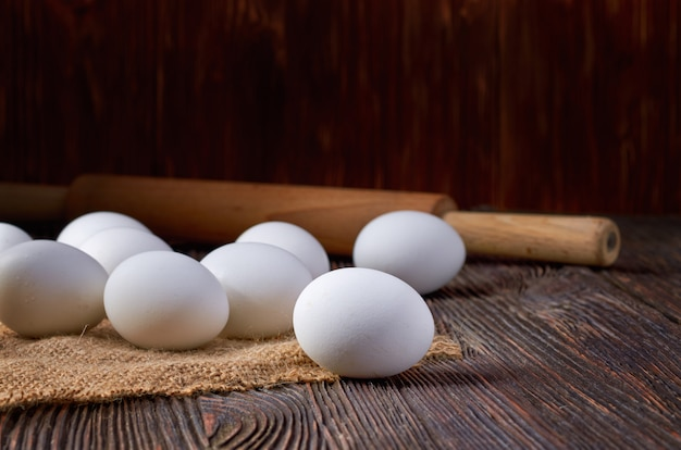 White eggs on burlap and wooden table. in the background, a rustic rolling pin. low key.