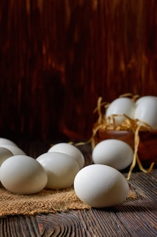 White eggs on a burlap and wooden table, eggs in a wooden bowl in the background. low key.