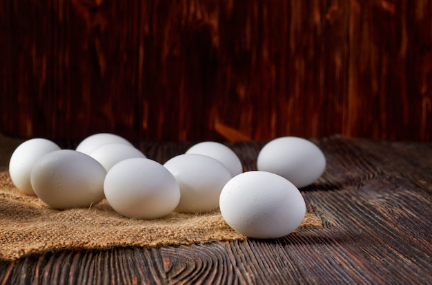 White eggs on burlap and wooden table. low key.