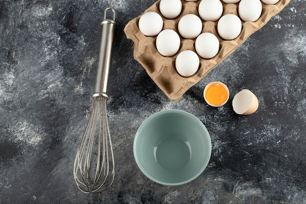 White eggs in carton container, bowl and whisker on marble surface.