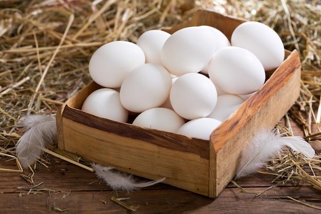 Белые яйца в коробке на деревянном столе