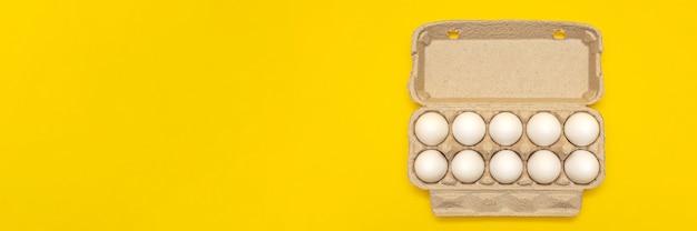 노란색 배경에 골 판지 상자에 흰색 달걀