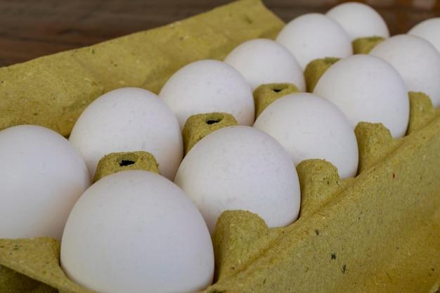 Белые яйца в картонной коробке, выборочный фокус