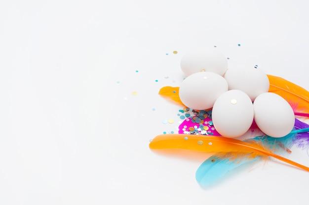 コピースペース付きの白い背景の上のカラフルな羽の白い卵。イースターのコンセプトです。
