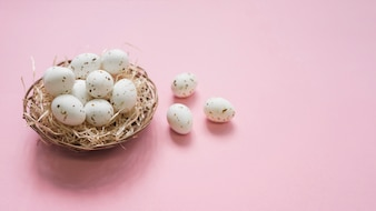 ピンクのテーブルの上の巣に白い卵