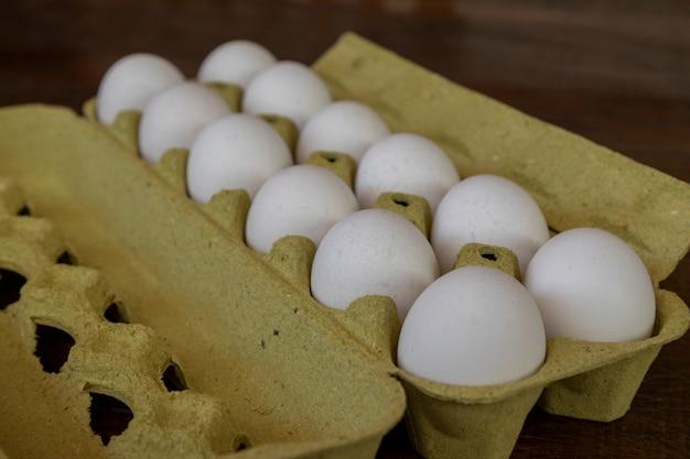 Белые яйца в упаковке для продажи, выборочный фокус