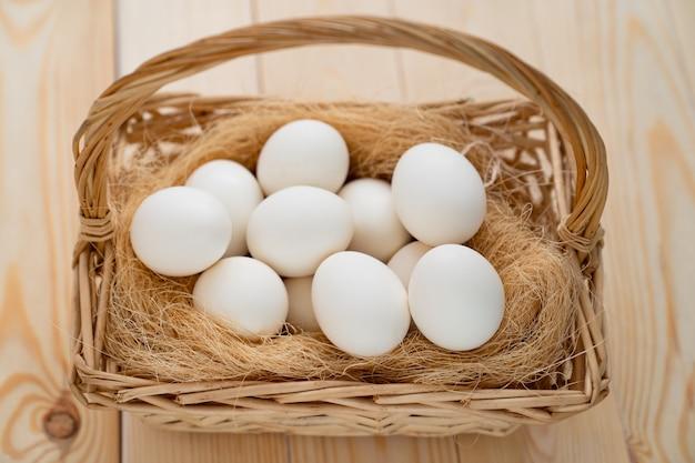 Белые яйца в корзине разбросаны на деревянном столе. продукция фермы.