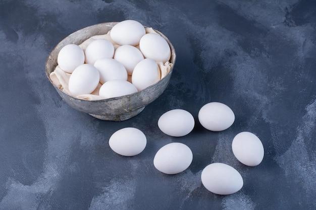 Uova bianche in una tazza di carne sul tavolo blu.