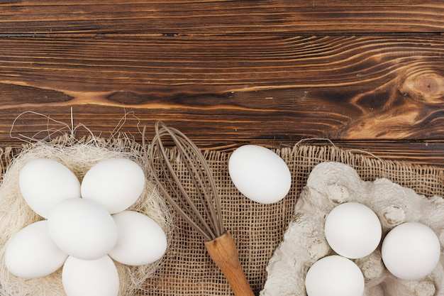 White eggs in nest and in rack with whisk on table