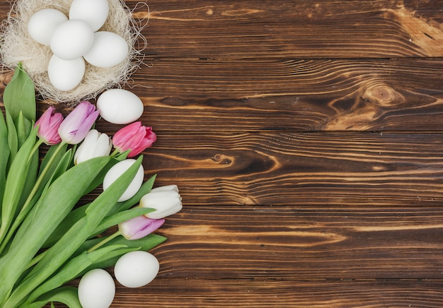 White eggs in nest with bright tulips on wooden table