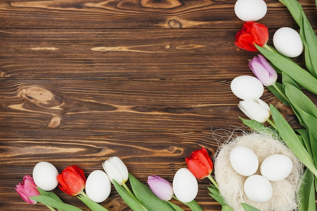 White eggs in nest with tulips on brown wooden table