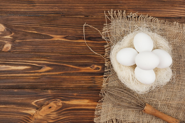 White eggs in nest with whisk on table